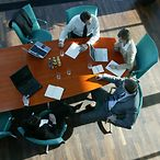 Geschäftsleute am Tisch/ Bird's-eye view of businesspeople at a table